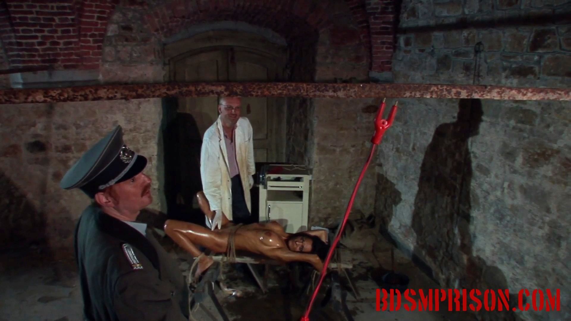 Natalia endures domination rope bondage medical play. Natalia was arrested for being an undercover agent and imprisoned. Her punishment will be harsh, worse than her interrogation. A prison guard and a mad doctor will take on the task of her sex slave training. She has to be washed first. They tie her down to a wood slab with rough rope.